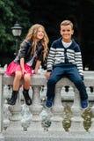 Två gulliga ungar sitter på räcket Marmor-sten springbrunn royaltyfri foto