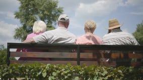 Två gulliga vuxna par som sitter på bänken och tillsammans talar Moget folk som vilar det fria gladlynt pension?r stock video