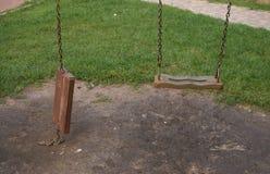Två gungor på lekplats för barn` s Royaltyfri Foto