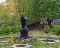 Två hägerstatyer på en sockel på en springbrunn i höstdagen royaltyfri fotografi