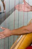 Två händer av en harpist på en harpa Royaltyfri Fotografi