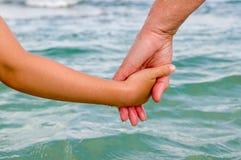 Två händer av ett barn och en äldre person arkivbild