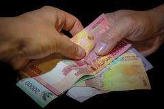 Två händer, en indones och en av Caucasian vit som till varandra räcker över indonesiska sedlar arkivfoto
