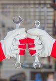 Två händer i handskar med skiftnyckeln Arkivbild