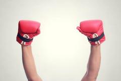 Två händer lyftte i de bärande boxninghandskarna för luft royaltyfri bild
