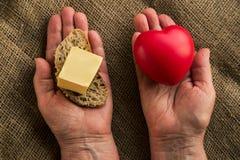 Två händer med hjärta på ett hand och smör på annat Arkivbilder