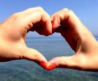 Två händer som formar en hjärta arkivfoton