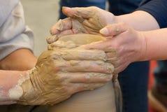 Två händer som gör krukmakeri Arkivbilder