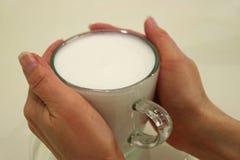 Två händer som rymmer en kopp av varmt, mjölkar tjänat som i en genomskinlig Glass kopp Arkivbilder
