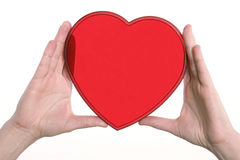 Två händer som rymmer en röd plast- hjärta isolerad på vit Arkivbilder