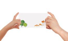 Två händer som rymmer som är pappers- med abstrakt stadsbakgrund och utrymme för text Fotografering för Bildbyråer