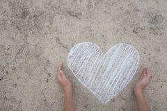 Två händer som skyddar vit hjärtaform Arkivbilder