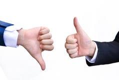 Två händer som upp signalerar tummar och tummar ner Royaltyfri Bild
