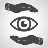 Två händer tar omsorg av ögonsymbolen Arkivfoton