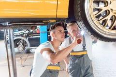 Två hängivna auto mekaniker som trimmar en bil till och med modificatien royaltyfria foton