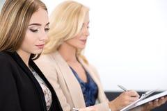 Två härliga affärskvinnor som sitter på seminariet och skriver något Arkivfoton