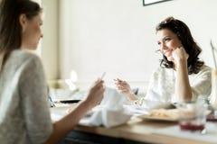Två härliga damer som äter i en restaurang, medan ha en conve arkivfoton