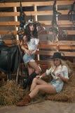 Två härliga flickor, blondin och brunett, med landsblick, sköt inomhus i stallet, lantlig stil Attraktiva kvinnor med hattar Royaltyfri Foto