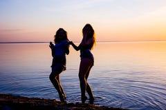 Två härliga flickor dansar på stranden på solnedgångbackgroun Arkivfoto