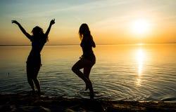 Två härliga flickor dansar på stranden på solnedgångbackgroun Royaltyfri Fotografi