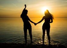 Två härliga flickor dansar på stranden på solnedgångbackgroun Arkivfoton
