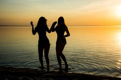 Två härliga flickor dansar rymma händer på stranden på su Royaltyfri Bild