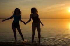 Två härliga flickor dansar rymma händer på stranden på su Royaltyfria Bilder