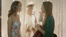Två härliga flickor diskuterar någon och skrattar i köpcentret stock video