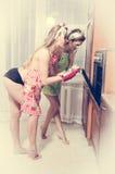Två härliga flickor för förföriska unga utvikningsbrudkvinnor på köket nära ugnen Royaltyfria Bilder
