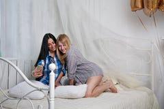 Två härliga flickor för flicka som gör ett selfiefoto på en telefon på ett b Fotografering för Bildbyråer