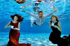 Två härliga flickor i en röd och Bourgogneklänning och en grabb i ett vit skjortabad och lek som är undervattens- i pölen De rymm royaltyfri foto