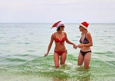 Två härliga flickor i juljultomtenhatt på stranden Royaltyfri Fotografi