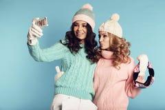 Två härliga flickor i varm hemtrevlig kläder som har gyckel i studio arkivfoto