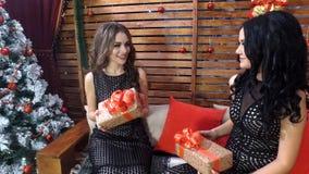 Två härliga flickor med långt hår i gulliga svarta klänningar meddelar med ferieaskar i händer för jul eller nytt år fotografering för bildbyråer
