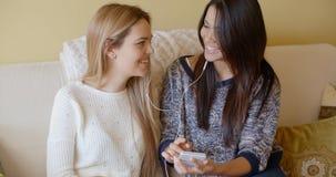Två härliga flickor på soffan lyssnar till musik royaltyfria foton