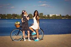 Två härliga flickor på stranden med cykeln royaltyfria foton