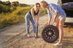Två härliga flickor reparerar ett bilhjul på en landsväg i strålarna av solnedgången arkivfoto