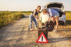 Två härliga flickor reparerar ett bilhjul på en landsväg i strålarna av solnedgången royaltyfria foton
