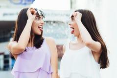Två härliga flickor som har gyckel på gatan Arkivfoto