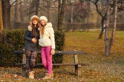 Två härliga flickor som har roligt utomhus- på solig höstdag Arkivfoto