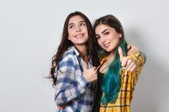 Två härliga flickor som ler upp och visar tummar På vitbakgrund arkivbilder