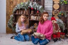 Två härliga flickor som poserar i julpynt Arkivfoto