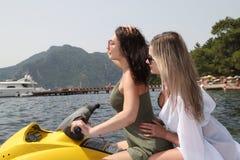 Två härliga flickor som rider en stråle, skidar på havet Royaltyfri Bild