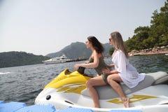 Två härliga flickor som rider en stråle, skidar på havet Fotografering för Bildbyråer