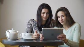 Två härliga flickor som sitter i kafé och att se en minnestavlaPC och ett skratt Kameraspioner lager videofilmer