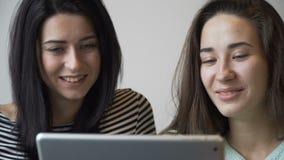 Två härliga flickor som sitter i kafé och att se en minnestavlaPC och ett skratt Närbild lager videofilmer