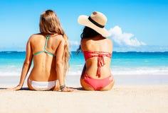 Två härliga flickor som sitter på stranden Arkivfoto
