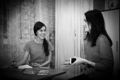 Två härliga flickor som sitter på tabellen som spelar kort, UNO Royaltyfri Bild