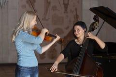 Två härliga flickor spelar basfiolen och fiolen royaltyfria foton