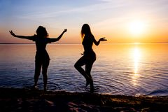 Två härliga flickor, studenter dansar på stranden på solnedgången Arkivbilder